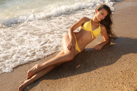 latin girls: fashion outdoor photo of sexy beautiful girl with dark hair in yellow swimsuit relaxing on beach Stock Photo