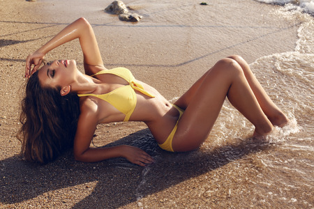 young bikini: fashion outdoor photo of beautiful woman with dark hair in yellow bikini relaxing on summer beach