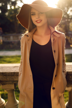 ladylike: fashion outdoor photo of beautiful woman with dark straight hair wearing elegant coat and hat,posing in sunny rays in autumn park