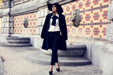 fashion outdoor foto van mooie ladylike vrouw met donker haar dragen van elegante jas en vilten hoed en poseren in de herfst park Stockfoto