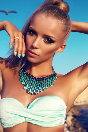 fashion outdoor photo of beautiful sensual woman with blond hair and bright makeup,wearing blue bikini and luxurious neklace
