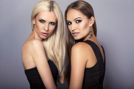 chicas guapas: moda foto de estudio de dos hermosas chicas sexy con cabello de lujo y maquillaje brillante