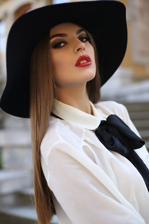 ladylike: fashion outdoor photo of beautiful ladylike woman with straight dark hair wearing elegant blouse and black hat