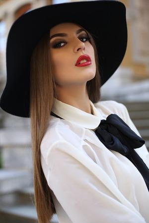 0e3138d0bb  33907520 - Moda foto al aire libre de la mujer hermosa dama con cabello  oscuro recta vistiendo elegante blusa y sombrero negro