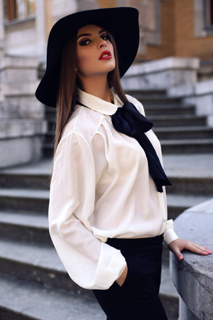 ladylike: fashion outdoor photo of beautiful ladylike woman with dark hair wearing elegant blouse and felt hat,posing on stairs in autumn park