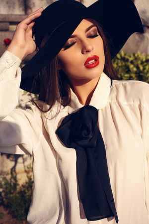 ladylike: fashion outdoor photo of beautiful ladylike woman with dark hair wearing elegant blouse and black hat,posing in autumn park Stock Photo