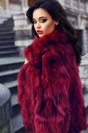 sexy glamour: fashion outdoor photo of sexy glamour woman with dark hair wearing luxurious red fur coat,posing on stairs in autumn park