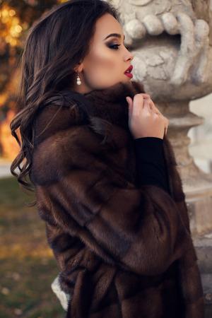 manteau de fourrure: mode photo en plein air de la belle femme glamour avec des cheveux noirs dans le manteau de fourrure de luxe posant dans le parc de l'automne
