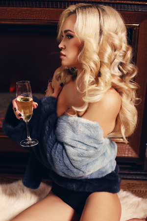 cosily: fashion interior photo of sensual beautiful woman with long blond hair with glass of champagne relaxing beside a chimney at bedroom