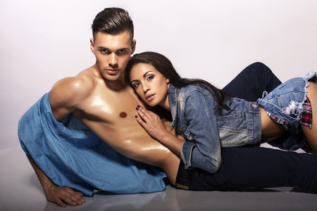 fashion photo of sexy impassioned couple in jeans clothes posing in studio