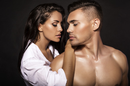 verliefd stel: mode foto van sexy gepassioneerde paar poseren in donkere studio Stockfoto