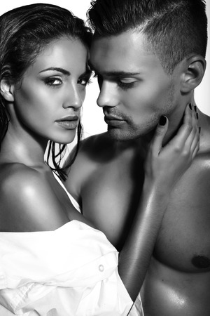 black and white fashion photo of sexy impassioned couple posing in dark studio Banque d'images