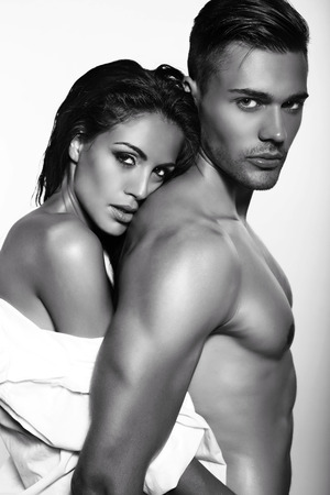 black and white fashion photo of sexy impassioned couple posing in dark studio Stock Photo
