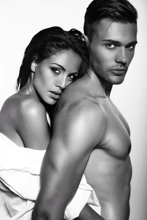 belle brunette: photo noir et blanc de la mode sexy couple passionn� posant en studio sombre