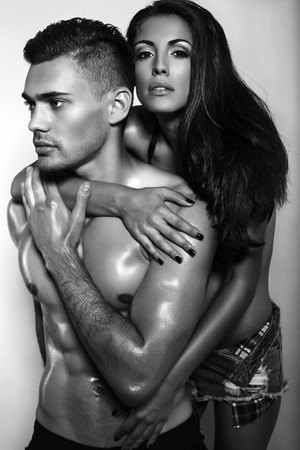 sensual couple: black and white fashion photo of sexy impassioned couple in jeans clothes posing in studio Stock Photo