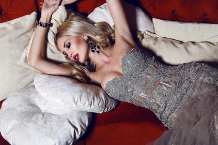 Foto interni di moda di donna bellissima con i capelli biondi in abito elegante sdraiato sul divano rosso in interni di lusso