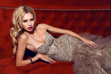 labios sensuales: moda foto interior de mujer hermosa con el pelo rubio en elegante vestido tumbado en el div�n rojo en interior de lujo