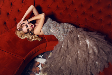 fashion interior photo of gorgeous woman with blond hair in elegant dress lying on red divan  in luxury interior Stockfoto