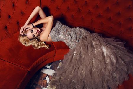 Foto interni di moda di donna bellissima con i capelli biondi in abito elegante sdraiato sul divano rosso in interni di lusso Archivio Fotografico - 37973185