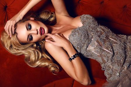 divan: Mode Innenraum Foto von wundersch�nen Frau mit blonden Haaren in einem eleganten Kleid liegend auf roten Sofa in Luxus-Interieur
