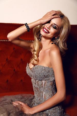 divan: moda foto interior de mujer hermosa con el pelo rubio en elegante vestido sienta en el div�n rojo en interior de lujo