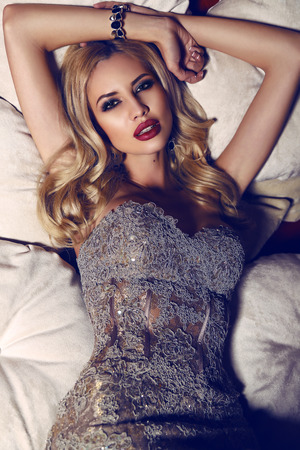 divan: fashion interior photo of gorgeous woman with blond hair in elegant dress lying on divan