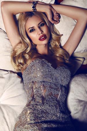 divan: moda foto interior de mujer hermosa con el pelo rubio en elegante vestido tumbado en el div�n Foto de archivo