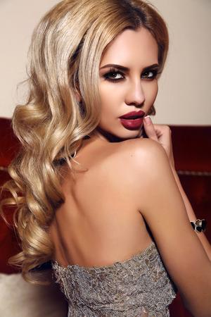 labios sensuales: moda foto interior de mujer hermosa con el pelo rubio y el maquillaje brillante, con un vestido de lentejuelas de lujo Foto de archivo