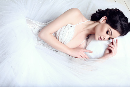 brides: fashion studio photo of beautiful elegant bride with dark hair in luxurious wedding dress