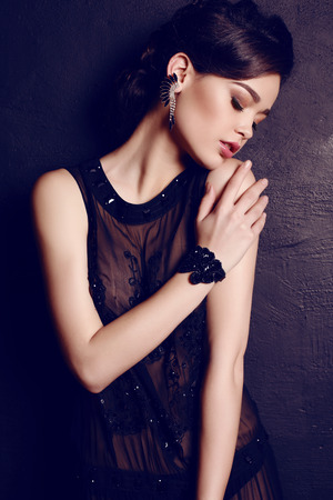 fashion studio photo of beautiful elegant woman with dark hair in luxurious black dress