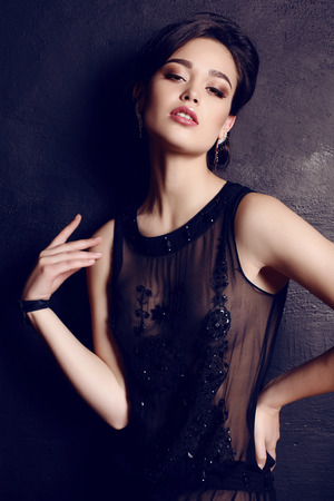 white dresses: fashion studio photo of beautiful elegant woman with dark hair in luxurious black dress
