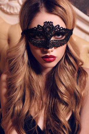 fashion interior photo of beautiful glamour woman with blond hair in lace black mask posing in bedroom