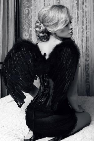 검은 날개를 가진 고급스러운 옷을 입고 금발 머리를 가진 아름 다운 섹시 한 여자의 흑백 패션 사진