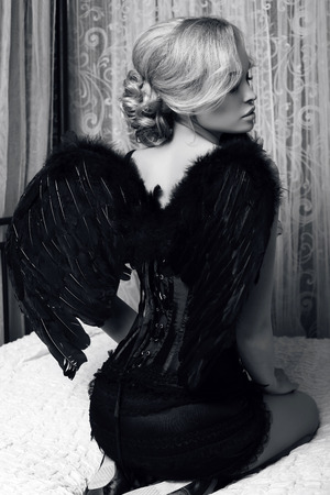 black and white fashion photo of beautiful sexy girl with blond hair in luxurious clothes with black wings Stock Photo