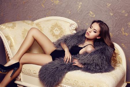 mode foto van mooie sensuele vrouw met luxe krullend haar het dragen van elegante bontjas, die zich voordeed in de slaapkamer Stockfoto