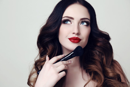brush in: fashion studio portrait of beautiful sexy woman with dark hair and bright makeup  holding cosmetic brush in hand Stock Photo