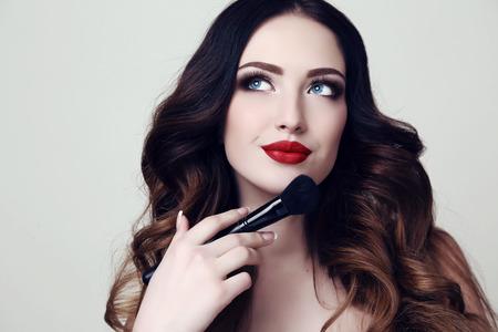 estudio de la moda retrato de la bella mujer sexy con el pelo oscuro y maquillaje brillante celebración de cepillo cosmético en la mano