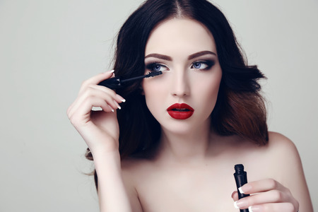 fashion studio portrait of beautiful sexy woman with dark hair and bright makeup with mascara Stock Photo