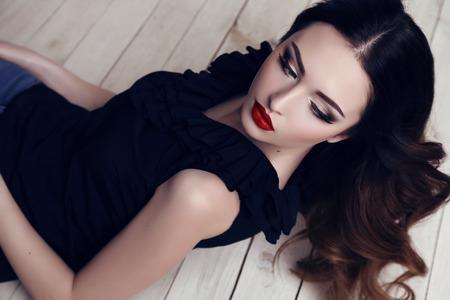 mujeres fashion: estudio de la moda retrato de la hermosa mujer sexy en elegante vestido negro con el pelo oscuro y maquillaje brillante