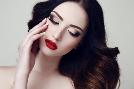 long red hair woman: fashion studio portrait of beautiful sexy woman with dark hair and bright makeup Stock Photo