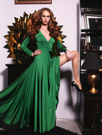 red haired woman: fashion photo of gorgeous red haired woman in elegant green dress posing in luxurious interior