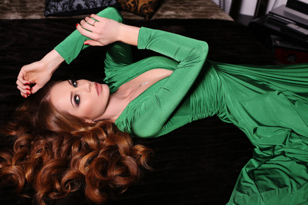 red haired: fashion photo of gorgeous red haired woman in elegant green dress posing in luxurious interior