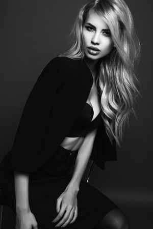 black and white fashion photo of beautiful sexy woman with blond hair in elegant black jacket posing in studio