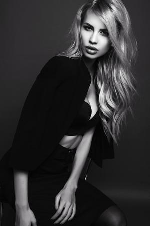 zwart-wit mode foto van mooie sexy vrouw met blond haar in een elegante zwarte jas poseren in studio