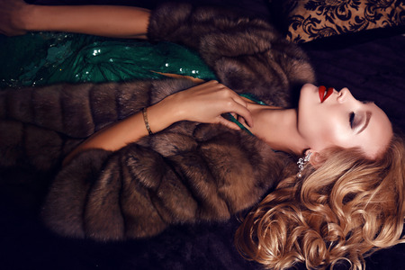 fashion photo of gorgeous blond woman in elegant  dress and fur coat posing in luxurious interior