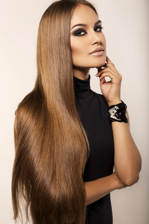 fashion studio portrait of beautiful woman with luxurious straight hair and evening makeup