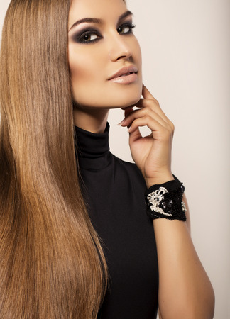 fashion studio portrait of beautiful sexy woman with luxurious straight hair and evening makeup Stock Photo