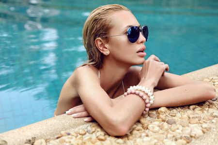 sunglasses beach: fashion photo of sexy beautiful woman with blond wet hair in aviator sunglasses posing in swimming pool