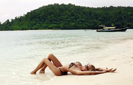wet bikini: fashion photo of sexy beautiful woman with blond wet hair in elegant bikini and sunglasses relaxing on tropical beach in Thailand