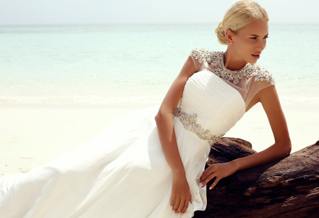 tanned woman: fashion photo of sexy beautiful woman with blond hair in elegant wedding dress posing on tropical beach in Thailand